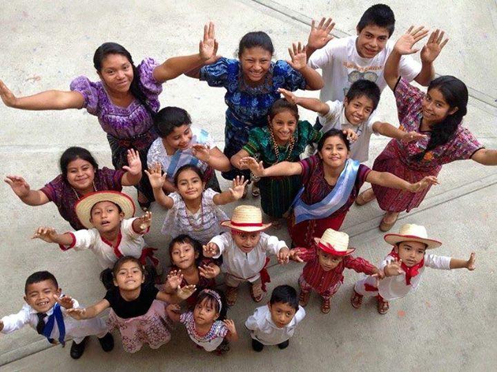 Believe Guatemala school children with hands up